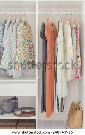 white closet with dress hanging on coat hanger at home - stock photo