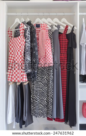 white closet with shirt and dress hanging at home - stock photo