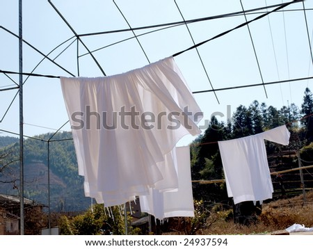 White cloth  drying on the clothesline . - stock photo