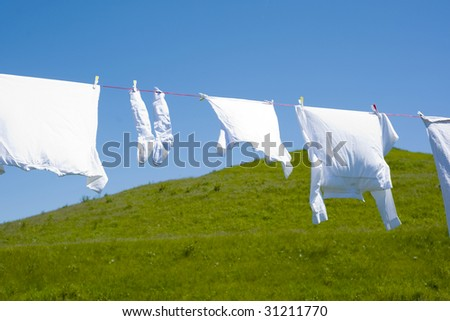 White clothes hanging on the line against blue sky and a green hill