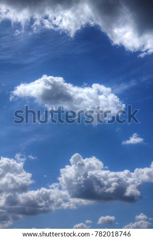 White clouds in the blue sky on a sunny day.