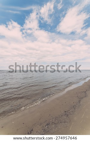 White clouds on the blue sky over country beach - retro vintage looking effect - stock photo