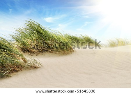 White clouds over dunes - stock photo