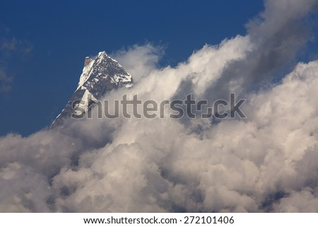 White clouds over Machhapuchchhre mountain - Fish Tail in English is a mountain in the Annapurna Himalya, Nepal - stock photo