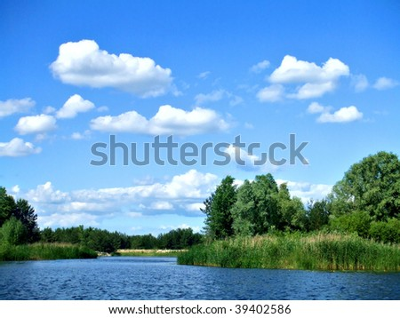 White clouds over the river - stock photo