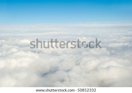 White clouds taken form above while flying in a plane.