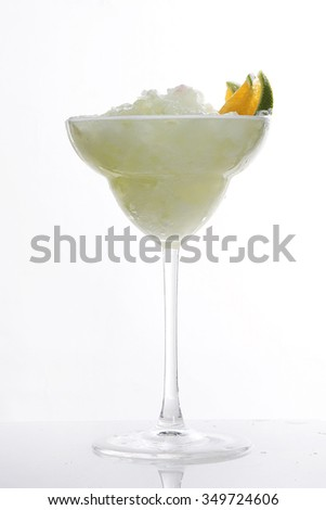 white cocktail in martini glass with lime on rim. fresh smoothie cocktail on white background. - stock photo