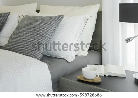 White coffee cup and book on wooden night table next to bed