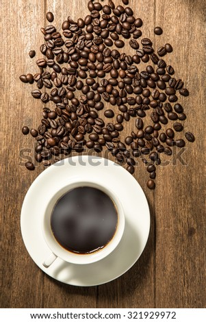 White coffee cup and coffee beans on wood background. - stock photo