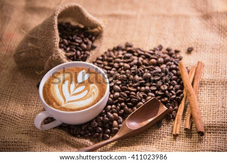 white coffee cup and roasted coffee beans around - stock photo