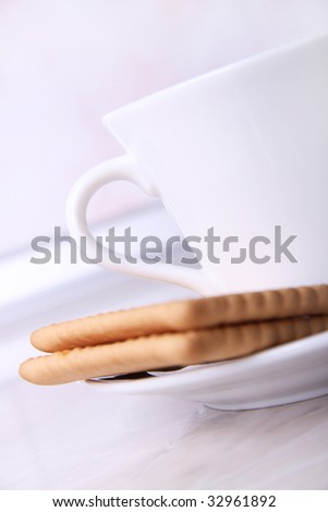 White coffee cup and two biscuits on table. Detail from the kitchen.