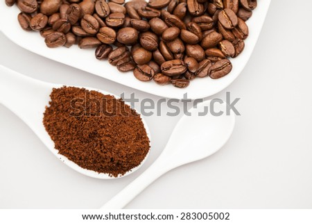 White coffee cup, coffee plate and teaspoon with coffee beans and coffee powder