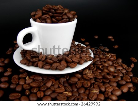 White coffee cup full of coffee beans on a black background