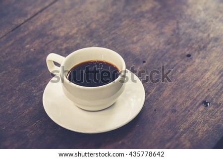 White Coffee Cup on a Wooden Table (Vintage filter effect used) - stock photo