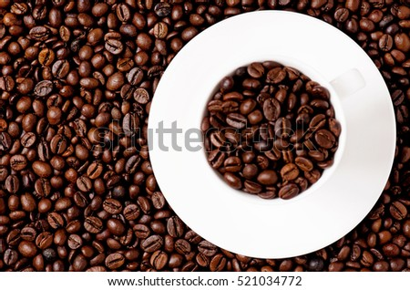 White coffee cup on coffee beans - top view - focus on background
