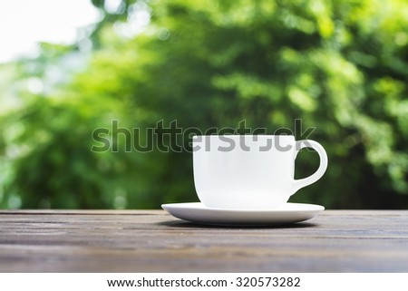 White coffee cup on wooden bench and green bokeh background
