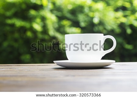 White coffee cup on wooden bench and green bokeh background - stock photo