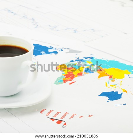 White coffee cup over world map and financial documents - studio shot - 1 to 1 ratio