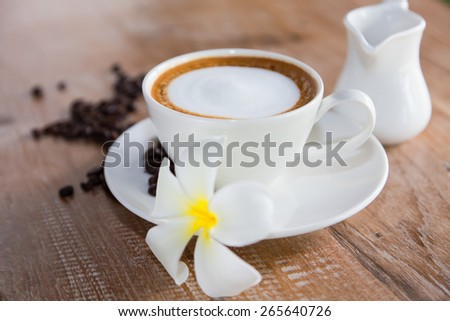 White coffee cup placed on the table with milk. - stock photo