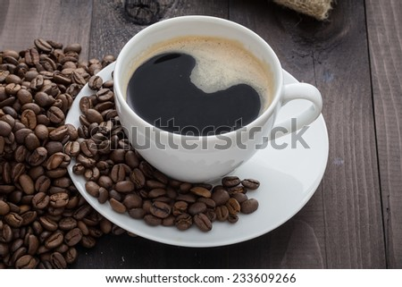 White coffee cup with coffee and around the cup lies coffee beans - stock photo