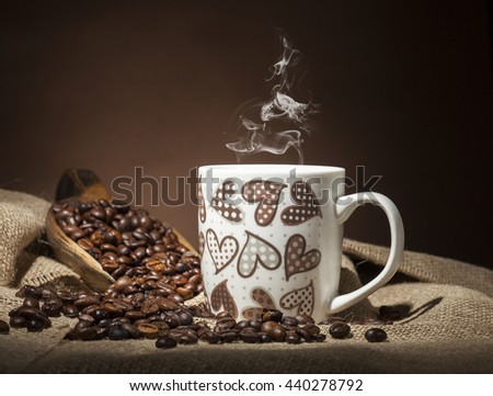 White coffee cup with hearts and coffee beans on burlap textile and brown background. - stock photo