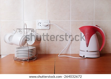 White coffee cups with saucers and electric kettle - stock photo