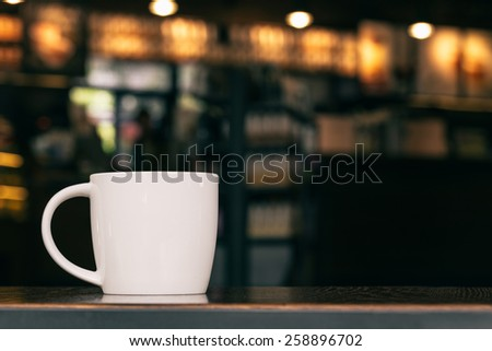 White Coffee Mug On Wooden Table In Cafe With Copyspace - stock photo