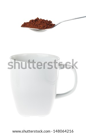 White coffee mug with a teaspoon of granulated instant coffee above the cup ready to be tossed into, isolated on white - stock photo