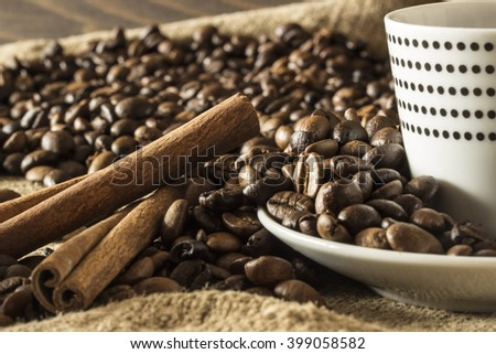 White Coffee mug with polka dots with coffee beans and cinnamon sticks.