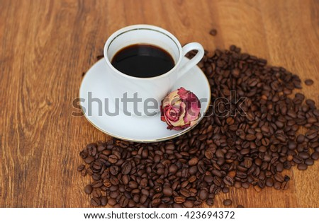 White Coffee mug with saucer and dried red rose and coffee beans on a wooden background closeup