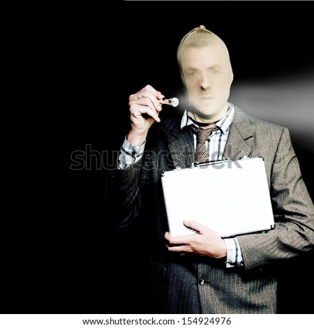 White collar corporate criminal in a business suit and stocking mask holding up a small portable torch and briefcase as he makes his way stealthily through the darkness at his work place - stock photo