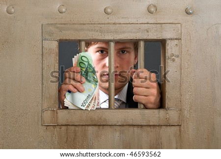 White collar criminal in jail for fraud, holding the bars with a substantial amount of cash in his hands - stock photo