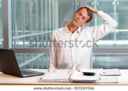white collar worker male relaxing neck  - short break for exercise in  office  - stock photo