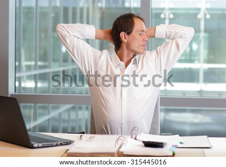 white collar worker male stretching arms, relaxing neck - short break for exercise on chair in office - stock photo
