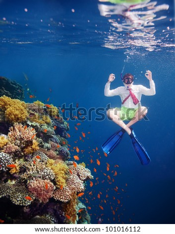 White collar worker man meditating underwater close to coral water with red tie and white shirt - stock photo