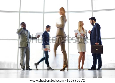 White collar workers communicating in office against window with their colleagues passing by