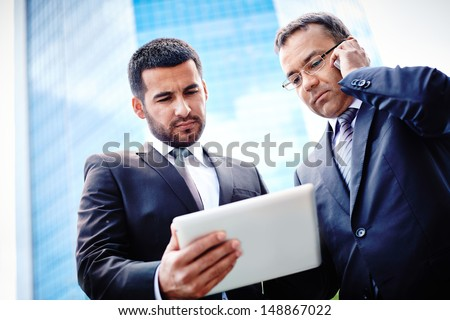 White-collar workers discussing business project in touchpad and consulting via mobile phone - stock photo