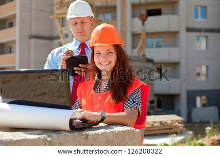 White-collar workers wearing protective helmet works on the building site