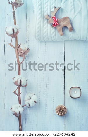 White collection of winter or Christmas decorations - knitted sweater, candle, fur tree and cotton branch, on wooden table. Toned photo. - stock photo