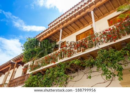 White colonial balcony in historic Cartagena, Colombia with red flowers on it - stock photo
