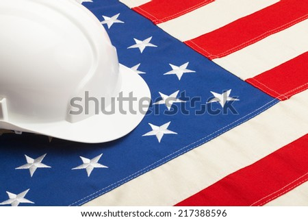 White color construction helmet laying over USA flag - closeup shoot