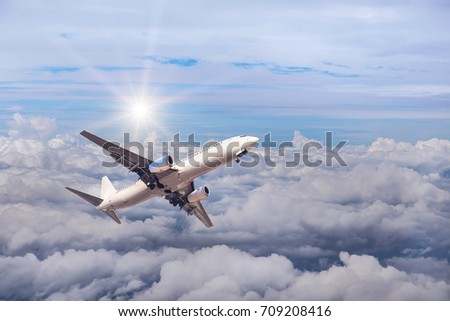 White commercial airplane flying away in to sky high altitude above the white clouds with sunlight travel destinations concept.
