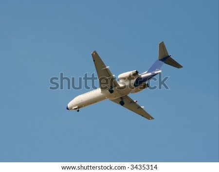 White commercial airplane landing against clear blue sky - stock photo