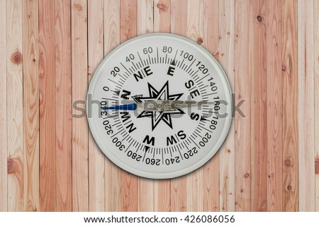 White Compass on wooden interior background - stock photo