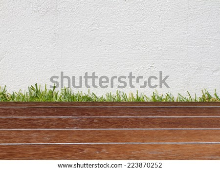 White concret wall and green grass on wood floor