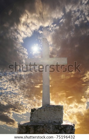 White concrete cross with a beautiful sunrise as background - stock photo
