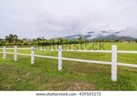 White concrete fence in farm field in rainy season - stock photo