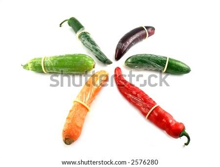 White condoms on different vegetables: pepper, carrot,  egg-plant, cucumber - stock photo