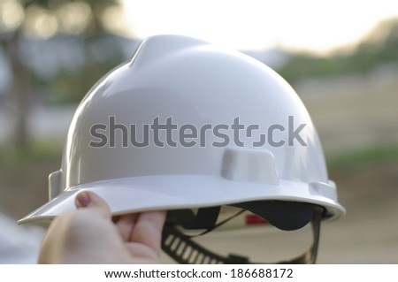 white construction hat with hand on site - stock photo