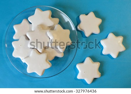 White cookies in the shape of stars on the transparent saucer and on blue background